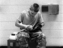 A young inmate polishes boots
