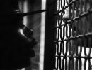 A drill instructor barks at a young man behind bars.