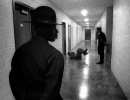 In a hallway a drill instructor watches as a young boot gives another DI 25 sit ups.