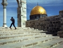 An Israeli soldier walks past the Dome of the Rock, Jerusalem.