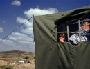 A Palestinian family look toward where their home once stood.